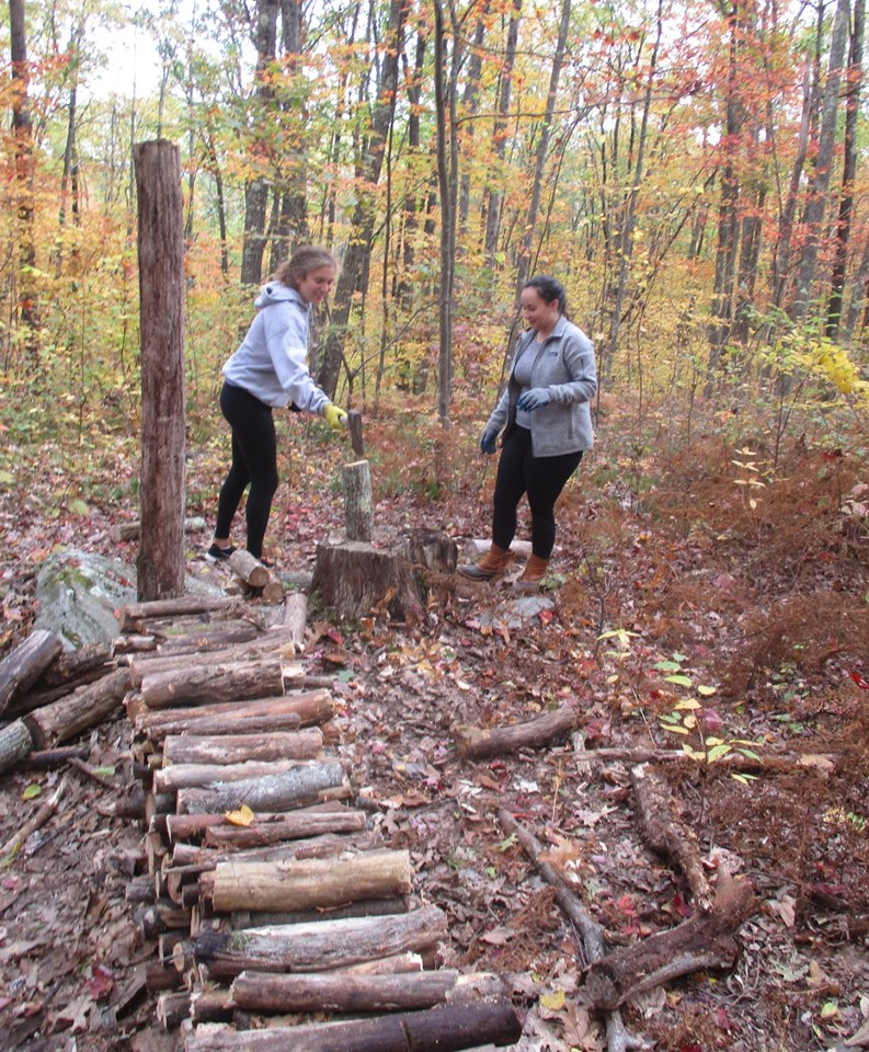 Holy Cross Students Eliza and Charlotte Splitting Wood at the Hermitage